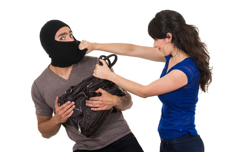 punching bag: beautiful young girl with hand bag punching masked male thief beautiful young girl with hand bag isolated on white