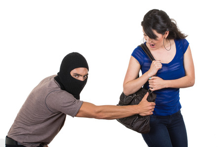 robbing: masked male thief robbing beautiful young girl with hand bag isolated on white