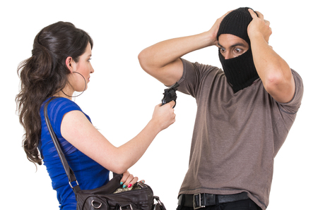 beautiful girl pointing gun at surprised masked male thief isolated on white