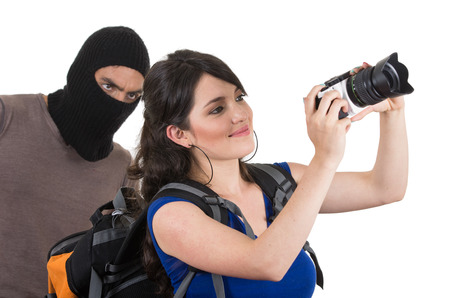 masked male thief robbing beautiful young happy girl carrying camera from behind photo