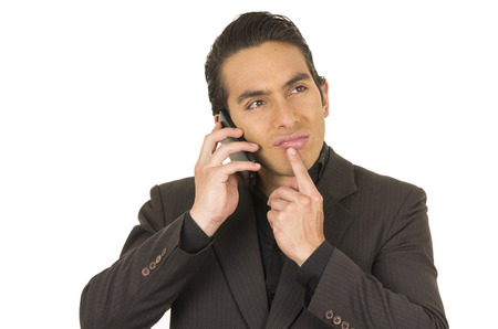 handsome elegant young latin man wearing a suit posing talking on cell phone mobile isolated on white photo