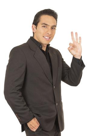 elegante Hombre latino joven y guapo que llevaba un traje posando gesticulando bien aislado en blanco