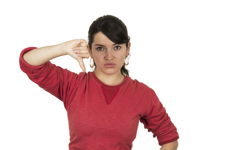decepci�n: bastante joven que llevaba rojo arriba posando sosteniendo el pulgar hacia abajo concepto de decepci�n aislado en blanco