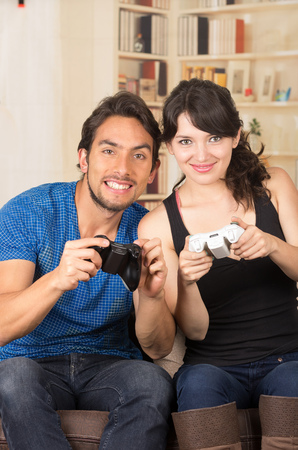 young cute smiling couple playing video games in livingroom photo