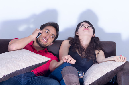 chats: bored girlfriend watching television while boyfriend chats on the phone Stock Photo