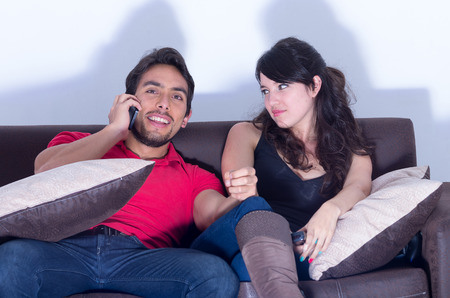 chats: bored girlfriend watching television while smiling boyfriend chats on the phone Stock Photo