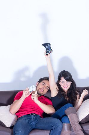 young cute couple playing video games having fun in livingroom photo