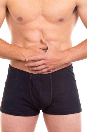 ulceras: Hombre descamisado muscular con dolor de est�mago aislado en blanco Foto de archivo