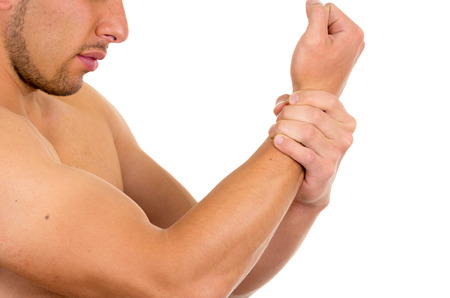 wrist pain: muscular shirtless man with wrist pain isolated on white Stock Photo