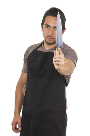 young knife: handsome young male chef wearing black apron holding knife isolated on white