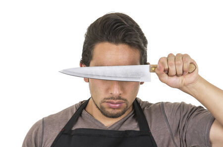 young knife: handsome young male chef wearing black apron holding knife in front of eyes isolated on white