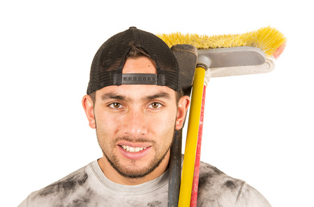 skilled labour: happy young muscular latin construction worker cleaner holding broom isolated on white
