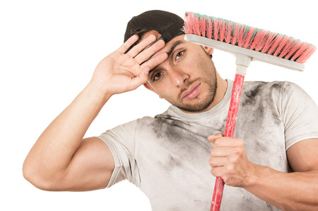 fixer: tired young muscular latin construction worker cleaner holding broom isolated on white