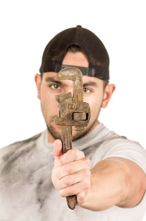 fixer: young muscular latin construction worker holding a wrench isolated on white