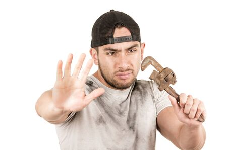 young muscular latin construction worker holding a wrench isolated on white photo
