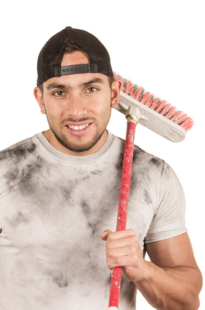 fixer: happy young muscular latin construction worker cleaner holding broom isolated on white