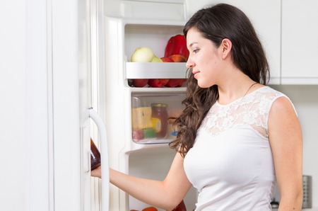 searching for: young beautiful brunette woman searching for food in the fridge