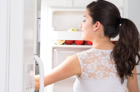 refrigerator with food: young beautiful brunette woman searching for food in the fridge