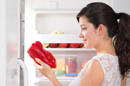 woman searching: young beautiful brunette woman searching for food in the refrigerator holding red pepper