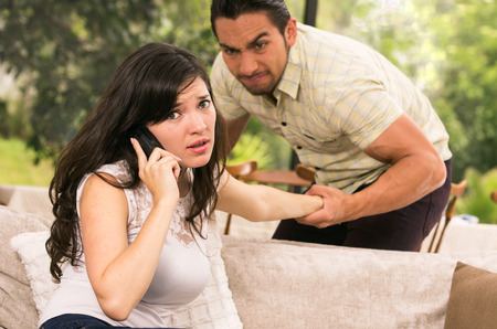 calling for help: married couple fighting having an argument at home wife calling for help concept of domestic violence
