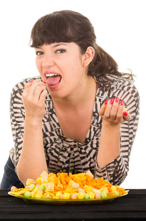 overeating: young hungry brunette girl overeating junk food