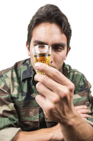 borracho: angustiada ptsd veterano soldado militar beber un trago de licor solated en blanco Foto de archivo