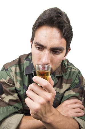 solated on white: distraught military soldier veteran ptsd drinking a shot of liquor solated on white Stock Photo