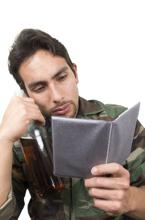 distraught: distraught military soldier veteran ptsd holding a bottle and looking at photos isolated on white
