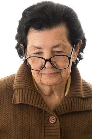 evocative: portrait of nostalgic sad grandmother looking down isolated Stock Photo