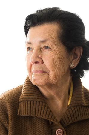 nostalgic: closeup portrait of grandmother looking to the side nostalgic