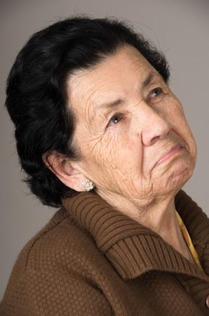 evocative: closeup portrait of old cranky grumpy sad woman grandmother