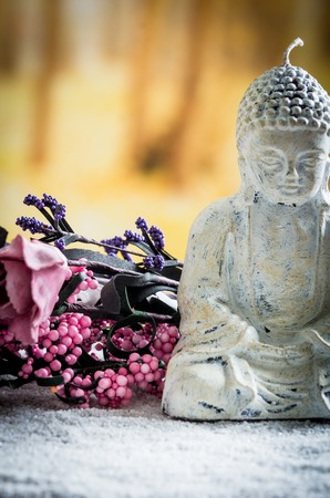 pebblestone: closeup of small sculpture of buddha over white pebbles with pink flowers in the background