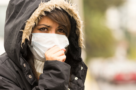 air pollution: portrait of young girl walking wearing jacket and a mask in the city street concept of  pollution
