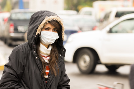 pollution: portrait of young girl walking wearing jacket and a mask in the city street concept of  pollution
