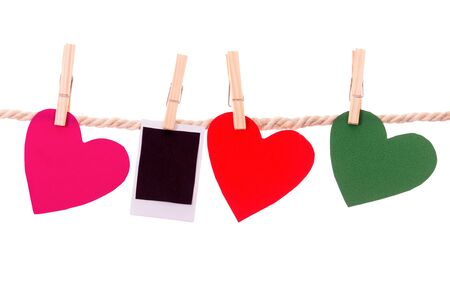 instant photograph and paper heart shapes hanging on a rope clothesline isolated on white photo