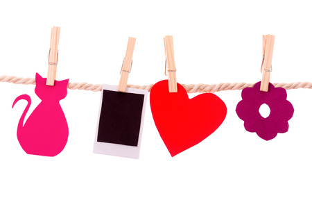 instant photograph and paper shapes hanging on a rope clothesline isolated on white photo