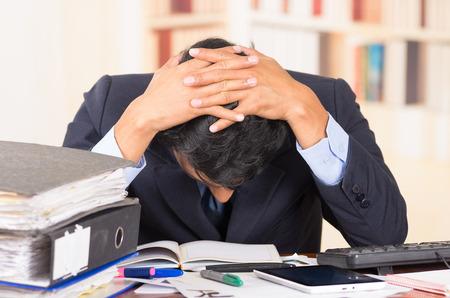 papeles oficina: joven estresado hombre de negocios abrumado con las pilas de carpetas en su escritorio con la cabeza mirando hacia abajo Foto de archivo