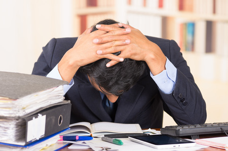 head down: young stressed overwhelmed business man with piles of folders on his desk holding his head looking down