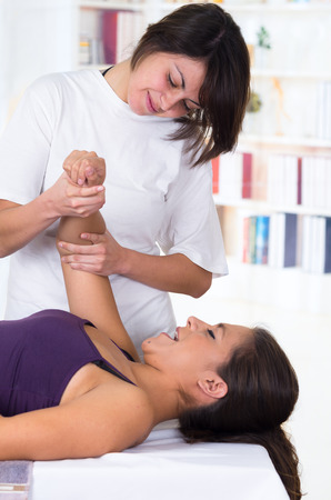 alternative therapy: young woman lying while getting a massage from specialist concept of physiotherapy Stock Photo