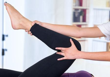 masaje deportivo: joven mujer tumbada mientras recibe un masaje desde el concepto especialista de la fisioterapia