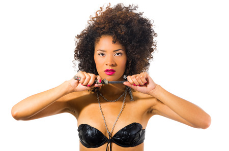 intimidating: beautiful exotic young tribal woman holding a dagger isolated on white Stock Photo