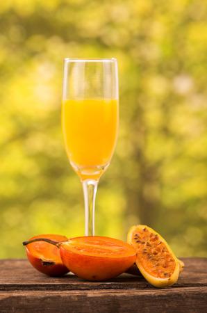 tomate de arbol: vaso de jugo con rodajas de tomate de árbol y maracuyá plátano sobre una mesa de madera sobre un fondo de bosque