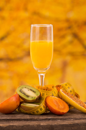 tomate de arbol: vaso de jugo con rodajas de kiwi, tomate de árbol y maracuyá plátano sobre una mesa de madera sobre un fondo amarillo