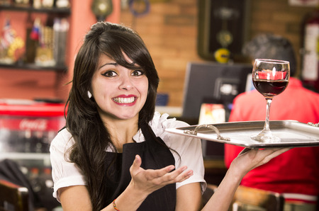 alcohol server: beautiful young waitress girl serving a drink holding tray