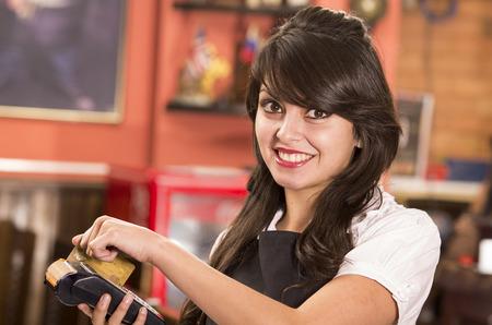 beautiful young friendly waitress swiping credit card