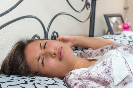 somnolent: cute sleepy young girl unwilling to get up from bed