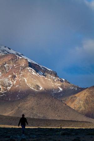 sillhouette: Tourist sillhouette walking along Chimborazo National Park in andean Ecuador, South America Stock Photo