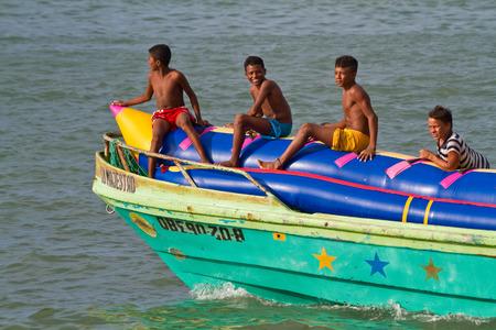 sua: SUA, ESMERALDAS, ECUADOR - JANUARY, 1, 2013: Unidentified young boys resting in an inflatable banana boat in Sua, Esmeraldas.