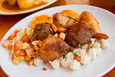 Fritada, fried pork, typical ecuadorian dish served with hominy, sweet plantain and potato tortillas Standard-Bild