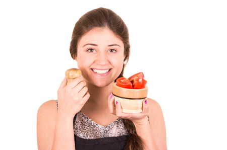beautiful young girl salting fresh tomatoes isolated on white photo